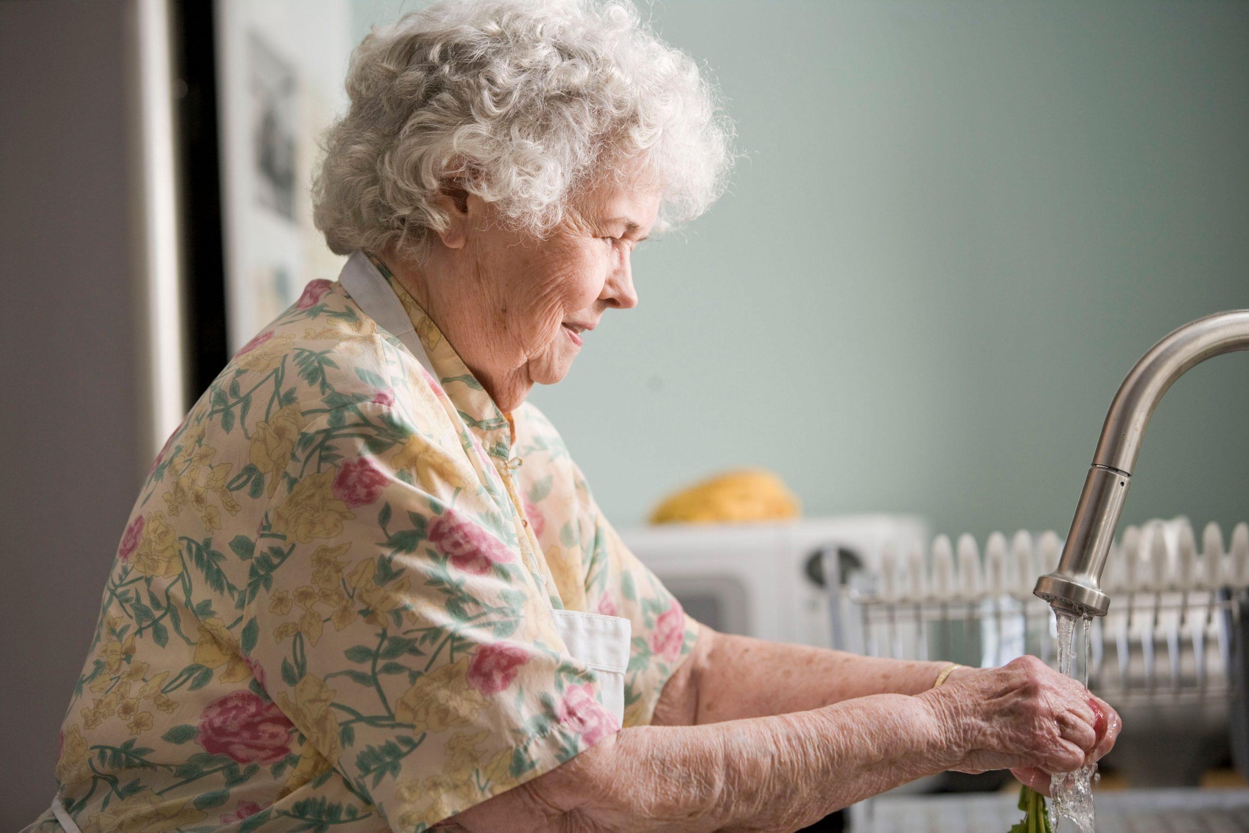 elder lady at sink washing hands