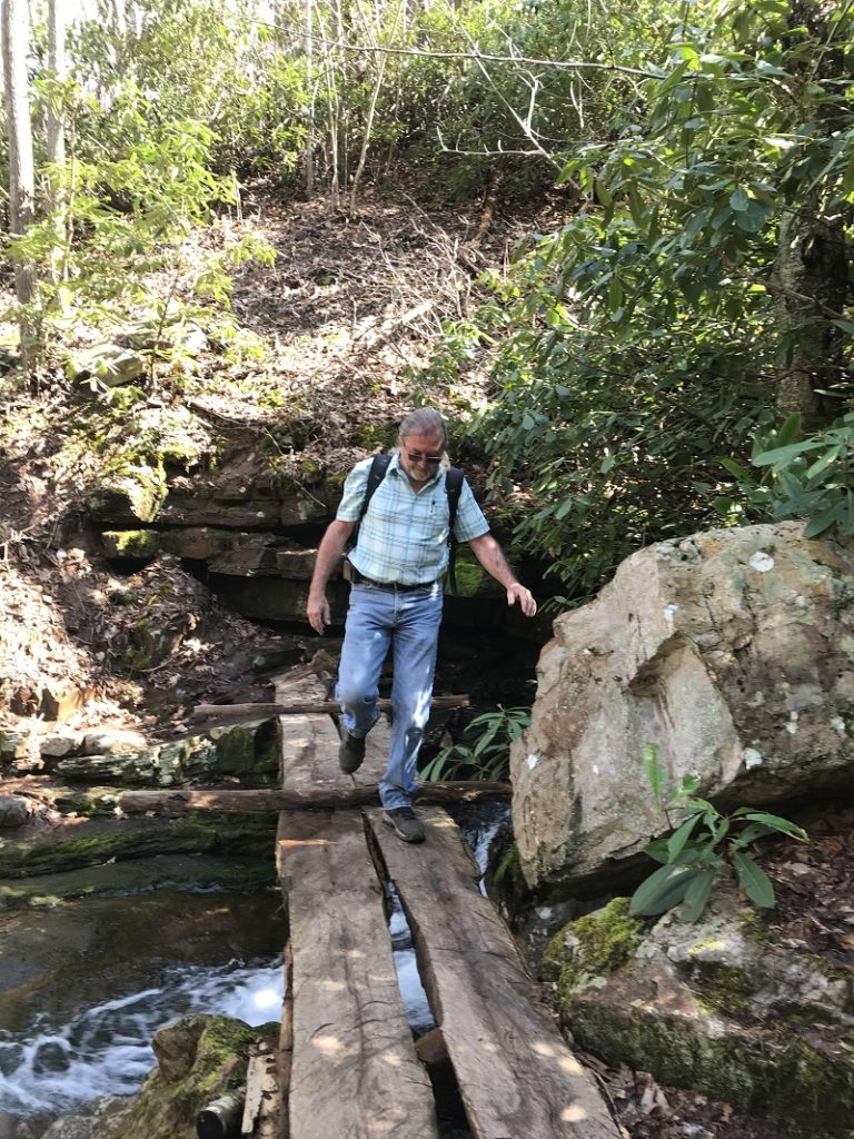 man walking on bridge in woods