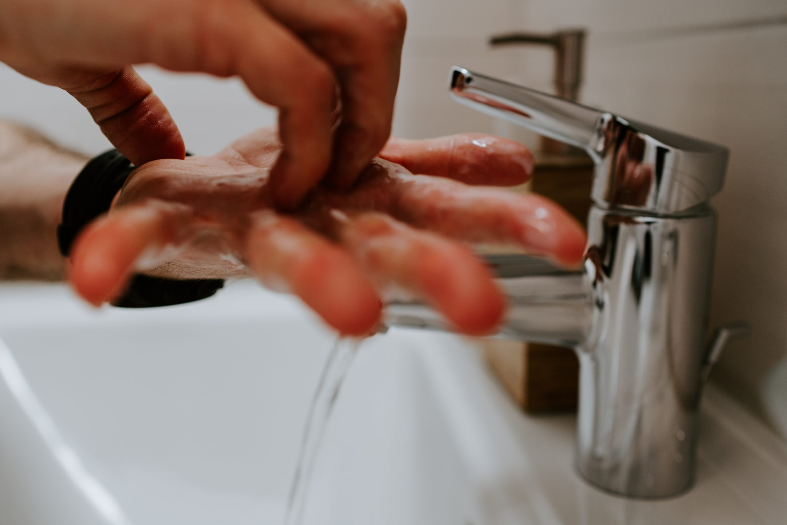 hand washing under faucet